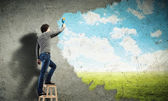 Young man drawing a cloudy blue sky — Stock Photo