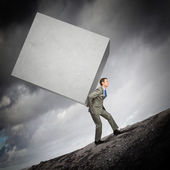 Businessman carrying cube — Stock Photo