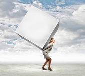 Businesswoman carrying cube — Stock Photo