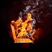 在火火焰的笔记本电脑 — 图库照片