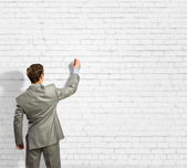 Businessman drawing sketches on wall — Stock Photo
