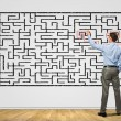 Businessman solving labyrinth problem — Stock Photo #30108755