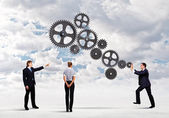 Business people and mechanism elements — Stock Photo