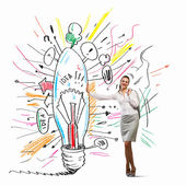 Businesswoman leaning on bulb — Stock Photo