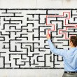 Businessman solving labyrinth problem — Stock Photo #30240577