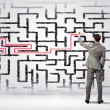 Businessman solving labyrinth problem — Stock Photo #30423991