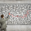 Businessman solving labyrinth problem — Stock Photo #30424161