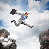 Businessman jumping over gap — Stock Photo