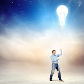 Adult man pulling rope with a bulb — Stock Photo