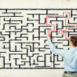 Businessman solving labyrinth problem — Stock Photo #30620607