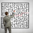 Businessman solving labyrinth problem — Stock Photo
