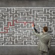 Businessman solving labyrinth problem — Stock Photo #30809363