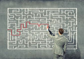 Businessman solving labyrinth problem — Photo