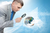 Man looking in magnifier — Stock Photo