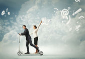 Businesspeople riding a scooter — Stock Photo