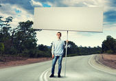 Teenager with banner — Stock Photo