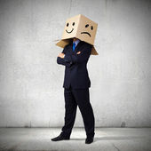 Businessman with box on head — Stockfoto