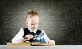 Schoolgirl examining opened book — Stok fotoğraf