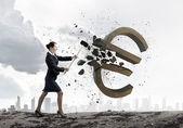 Businesswoman crashing stone euro symbol — Stock Photo
