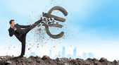 Businessman breaking stone euro symbol — Stock Photo
