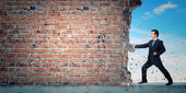 Businessman breaking stone wall — Stock Photo