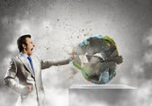 Businessman crashing Earth planet with punch — Stock Photo