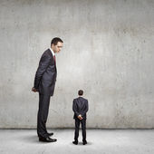 Businessman looking down at small businessman — Stock Photo