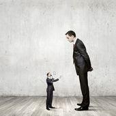 Businessman looking down at small businessman — Stok fotoğraf
