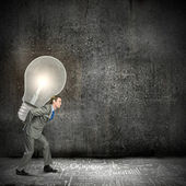 Businessman carrying big light bulb — Stock Photo