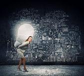 Businesswoman carrying big light bulb — Stock Photo
