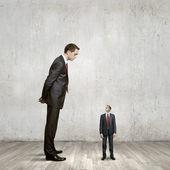Uomo d'affari guardando piccolo imprenditore — Foto Stock