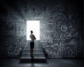 Businesswoman looking at opened door — Stock Photo