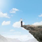 Businesswoman on edge of mountain — Stock Photo
