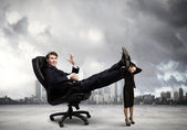 Businessman sitting in chair with legs on colleague — Stock Photo
