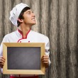 Cook holding blank chalk board — Stock Photo