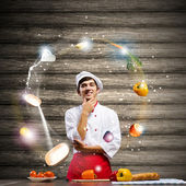 Cheerful cook and ingredients — Stock Photo