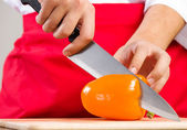 Hands cutting pepper — Stock Photo