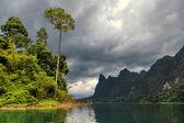 Isla iluminada por el sol en medio del lago cheo lan en tailandia — Foto de Stock