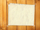Sheet paper on wooden wall — Stock Photo