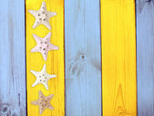 Starfishes on wood texture — Stock Photo