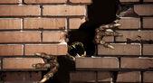 Patas do monstro, quebrando uma parede de tijolos — Fotografia Stock