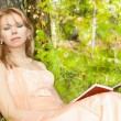 Attractive woman sleeping with book against a tree - Stock Photo