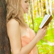 Beautiful woman with book in garden. Sun day - Stock Photo