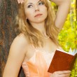 Beautiful woman with book near tree - Stock Photo