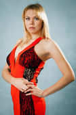 Femme blonde sexy en robe rouge permanent sur fond bleu — Photo