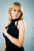 Thinking beautiful woman in black dress — Stock Photo