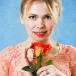 Young beautiful woman with a single red rose - Stock Photo