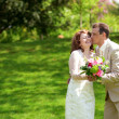Happy just married couple kissing in park at sunny day — Stock Photo