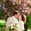 Just married couple is kissing under beautiful blooming tree — Stock Photo #12013108