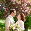 Beautiful newlywed couple in park at spring — Stock Photo
